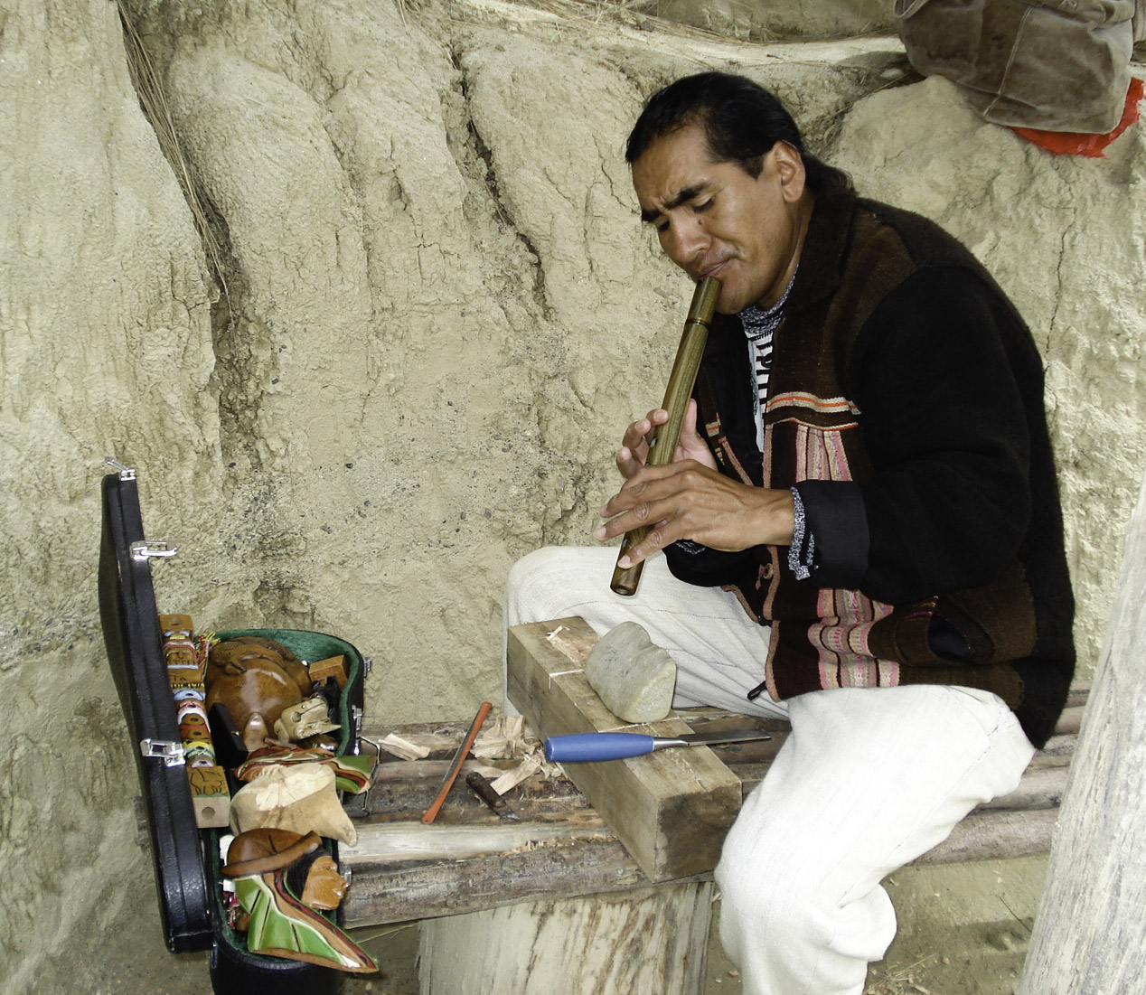 Instrument craftsman in Peru playing wooden flute