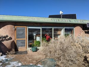 Earthships are earth coupled, insulated and built with recycled materials. Author looking out of an Earthship in Taos New Mexico